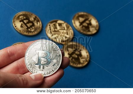 The hand holds a silver coin bitcoin on a blue background. The concept of crypto currencies.