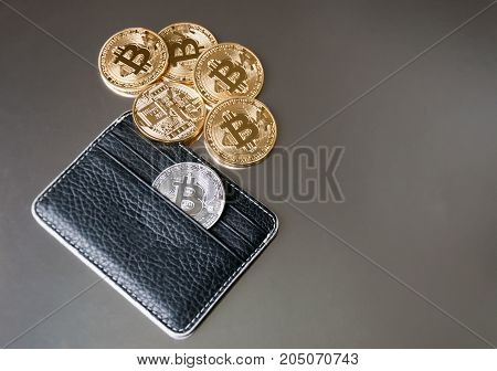 The black leather wallet on a dark background with several gold and silver coins of bitcoins falling out of their pockets. The concept of crypto currencies.