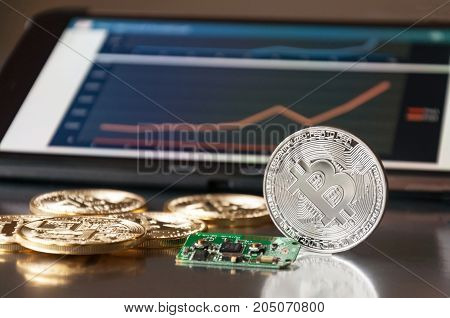 Few gold coins of bitcoins lie on the table in front of and next to the tablet on which charts of Bitcoin's cost growth are visible. One silver bitcoin stands side by side on the edge. The concept of crypto currency.