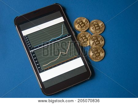 Few gold coins of bitcoins lie on the table in front of and next to the tablet on which charts of Bitcoin's cost growth are visible. Concept of crypto currency.