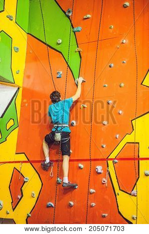 Man climber on artificial climbing wall in bouldering gym.