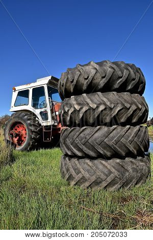 A pile of huge stacked tractor tires partially hides a tractor with a cab.