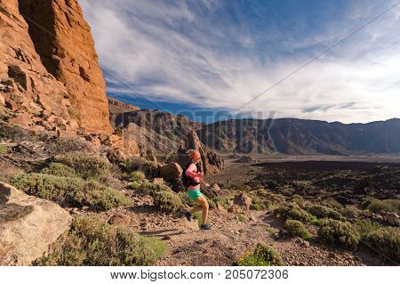 Trail running woman in mountains on rocky path. Cross country runner training with backpack in inspiring nature rocky footpath on Tenerife Canary Islands Spain.