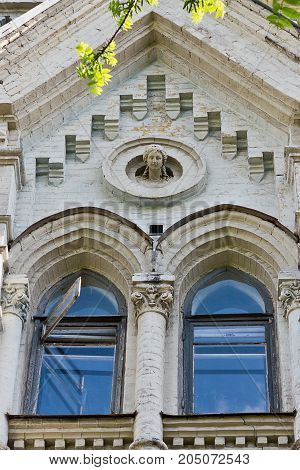 Part of an ancient building with windows and sculpture closeup. Architecture of Kiev