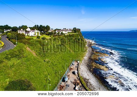 Atlantic coast with a steep cliff marina and Causeway Coastal Road at Ballycastle County Antrim Northern Ireland UK. Aerial view