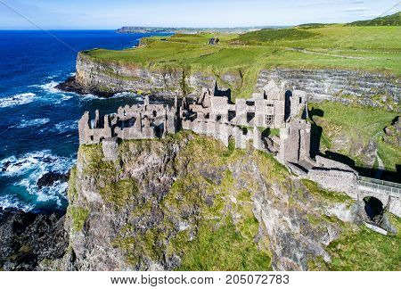 Ruins of medieval Dunluce Castle cliffs bays and peninsulas. Northern coast of County Antrim Northern Ireland UK. Aerial view.