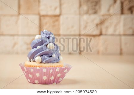 Colorful Cupcake On Table On The Brick Wall Background.