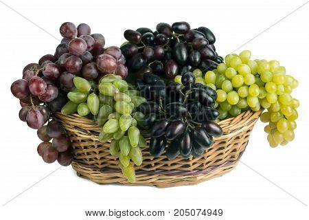 different varieties of fresh grapes in a basket on a white background