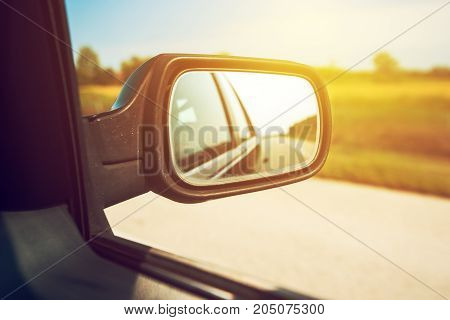 Car wing mirror driving down the motorway on sunny summer day