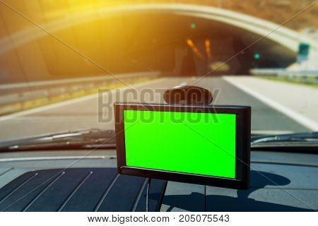 GPS navigation in the car mounted on vehicle windscreen window with green screen as copy space