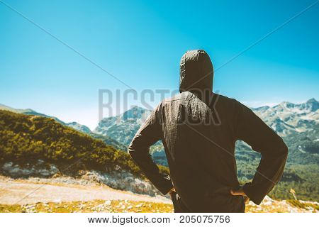Male tourist standing in mountain scenery and looking at beautiful landscape on sunny summer day