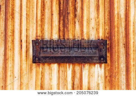 Weathered old rusty mail slot letterbox on metal doorway