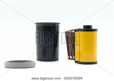 Black film bottle with gray bottle cap and yellow roll film on a white background.