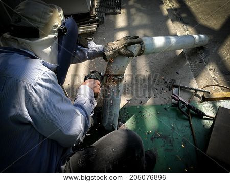 Worker man in personal protective equipment grinding pipe by grinder machine.