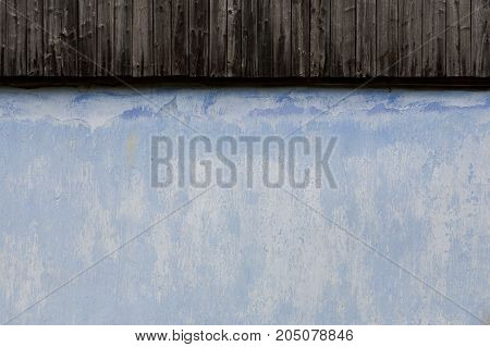 Surface of old house wall with historical paintings of blue color and a part of the wooden roof