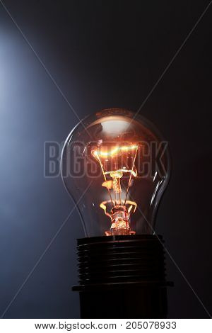 Closeup of one glowing lamp against dark background