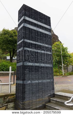 Street sign giving directions made out of slate in the historic Welsh mining town of Blaenau Ffestiniog in English and Welsh languages