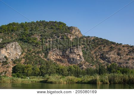 Rocky shores of the river Dalyan in Turkey with ancient Lycian tombs selective focus.