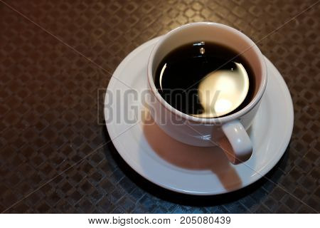 cup of black coffee at wood table at cafe.