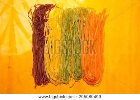 Overhead Of Traditional Italian Pasta Tagliatelle Of Different Colors On Yellow Background. Raw Tagl