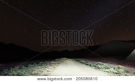 Night mountain road illuminated by car headlights