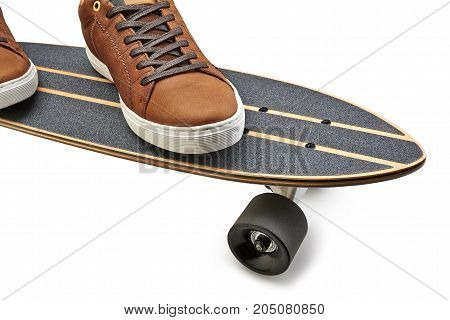 Side View Of A Black And Wooden Skate Board And Brown Leathers Shoes