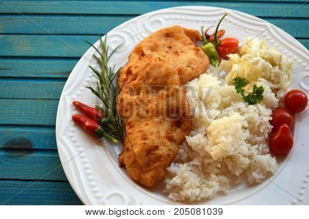 Viennese schnitzel on a cutting board on a wooden background.