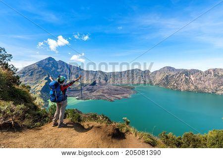 Hiker woman with blue backpack and trekking pole standing enjoy and happy with active volcano Baru Jari Lake Segara Anak