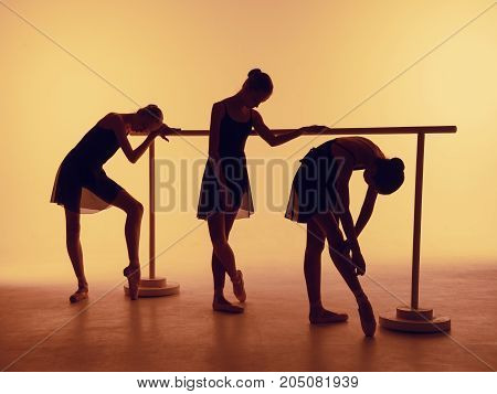 Composition from silhouettes of three young dancers in ballet poses on a orange background. The outline shooting - silhouettes of girls.