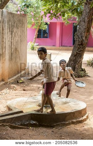 PONDICHERY PUDUCHERY INDIA - SEPTEMBER 04 2017. Unidentified boys girls children clean their plates after lunch at the outdoor canteen.