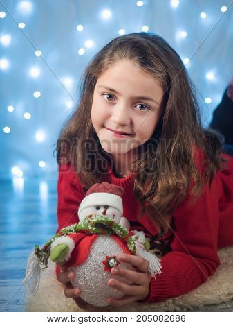cute little girl in the new year with a snowman in her hands