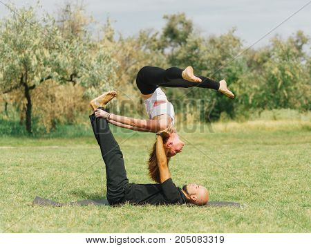 Women doing stretching workout in park outdoors at sunset. Beautiful woman and man practise yoga pose outside.