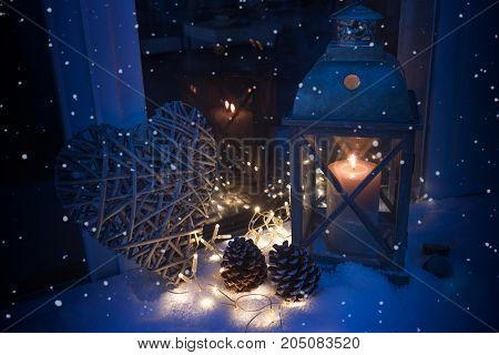 Winter decoration with snowflakes and a burning lantern in luminous blue light for a christmas night