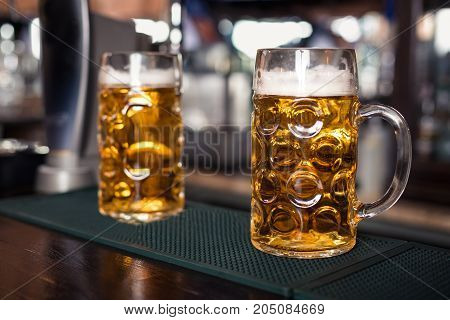 Two glasses of beer on a bar table. Beer tap on background. Still life. Oktoberfest