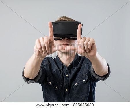 Man use virtual reality goggles and make frame on grey background