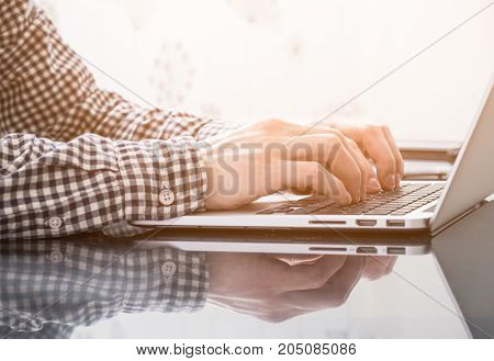 Hands typing on keyboard of laptop in office