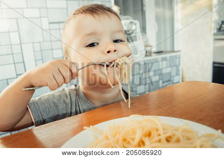 Baby In The Kitchen Eagerly Eating Pasta