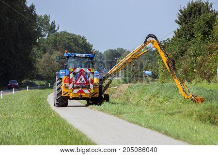 ACHTERHOEK NETHERLANDS - AUG 23 2013: Tractor mowing roadside grass shoulder.