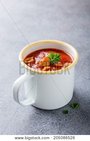 Delicious homemade tomato soup withmeat balls in enamel mug. Healthy food concept with copy space.