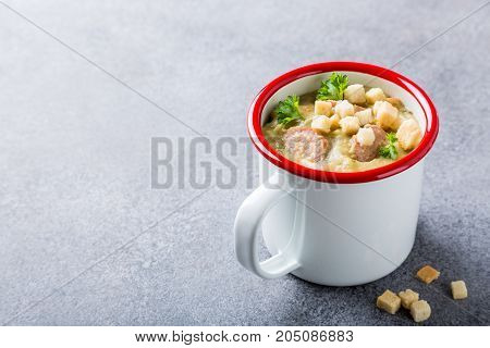 Delicious homemade pea soup with sausage and croutons in enamel mug. Healthy food concept with copy space.