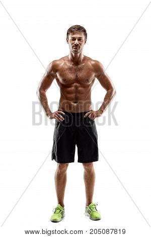 Portrait young sexy handsome man of strong athlete's body with bare torso. Dressed in a black sports shorts. Posing on white studio background
