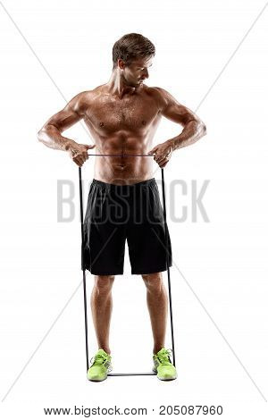 Handsome fitness man working out with rubber band, studio shot. Man in black shorts with a naked torso, isolated on white background