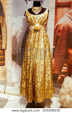 Riga, Latvia - August 2, 2011 - Evening golden dress with rose on the belt on fashion exhibition of 50s. Floral ornaments, gold roses embroidery lurex. Rare photo for magazines, articles, sites, web.