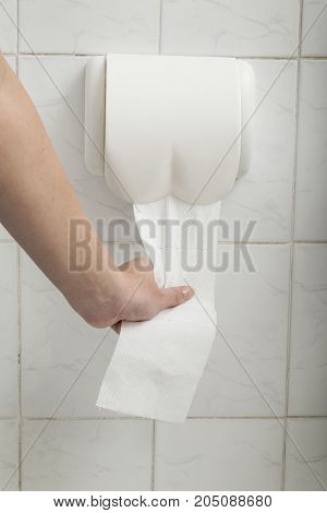 Detail of a woman's hand using toilet paper