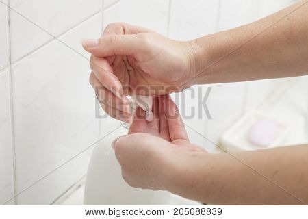Close up of a woman washing hands using liquid soap. Selective focus