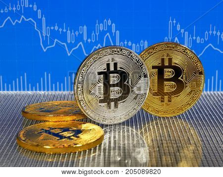 Golden and silver bitcoin coins on blue abstract finance background. Bitcoin cryptocurrency