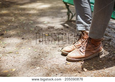 Young fashion hipster man's legs in brown leather boots and wearing gray jeans with both feet stepped on the floor ground concept of fashion and vintage lifestyle.