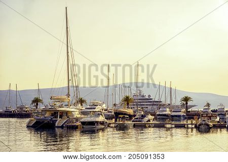 Beautiful Sunset At The Harbour. Yachts In Port With Mountains On The Background.