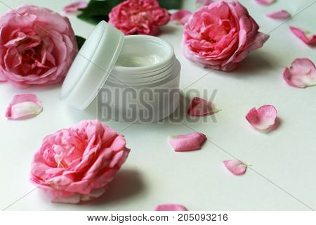 Cosmetic cream container and pink rose flowers on white background. Opened jar of facial or body cream with pink flowers and petals.