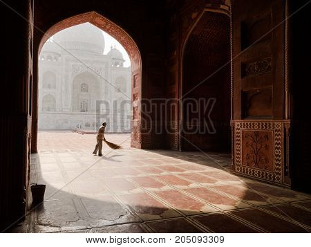 AGRA INDIA - circa MAY 2015: A man sweeps the prayer room in the Taj Mahal main mosque before the Friday prayer circa May 2015 in Agra India. The iconic Mughal mausoleum still serves as an active place of worship.